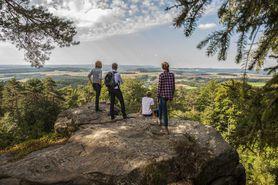 Eine Familie steht auf einem Felsvorsprung und blickt auf die Landschaft hinab.