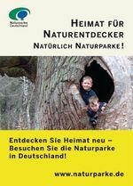 Anzeigenmotiv Heimat für Naturentdecker: Auf dem Foto gucken zwei Jungen aus einem hohlen Baum hinaus in die Kamera.