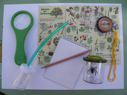 Die Inhalte der Naturpark-Entdecker-Weste liegen auf einem Tisch. Zu sehen sind: Eine Lupe, ein Insektenstaubsauger, ein Notizblock mit Stift, eine Becherlupe, ein Kompass und eine Bestimmungshilfe.