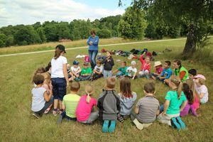 Wiesenexkursion der Naturpark-Spessart-Schule Partenstein: Die Schulkinder sitzen im Kreis auf einer Wiese