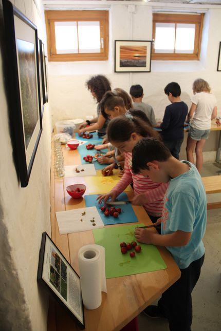 Auf dem Bild sind Kinder zu sehen, die an einem Tisch stehend Erdbeeren zubereiten