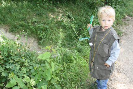 Ein kleiner Junge trägt eine Entdecker-Weste und hält eine Lupe in der Hand.