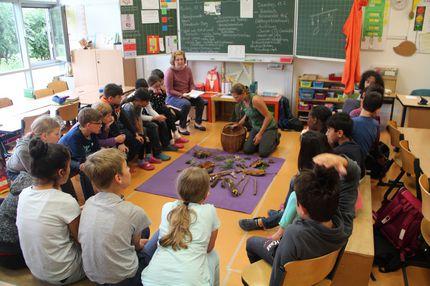 Die Schüler sitzen gemeinsam mit der Lehrerin im Stuhklreis. Vor Ihnen sind Naturmatierialien ausgelegt, die sie im Wald gesammelt haben
