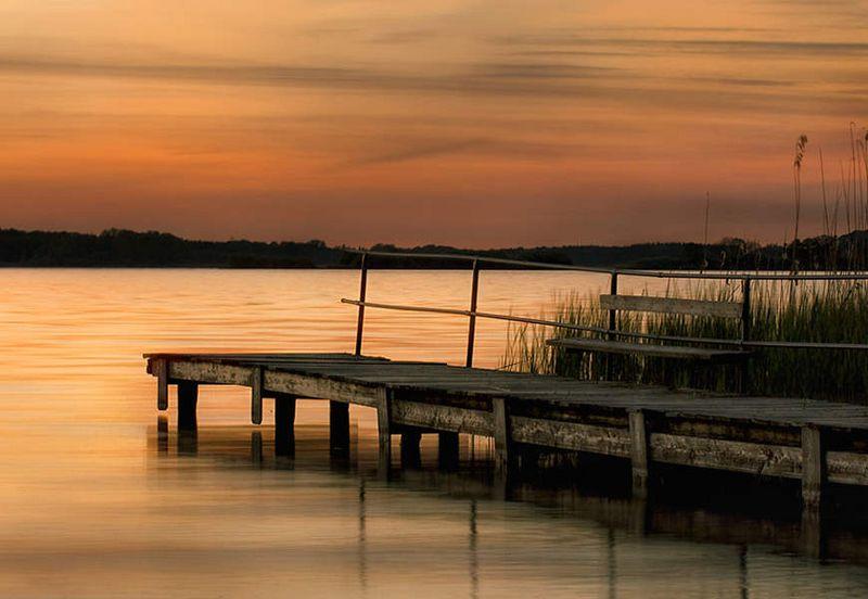 Im Vordergrund des Bildes ist ein Steg zu sehen, der in einen See führt. Der Himmel ist von der untergehenden Sonne orange gefärbt.