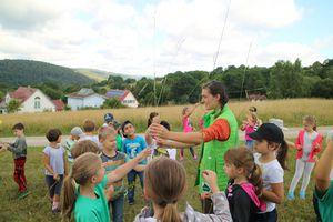 Wiesenexkursion mit Judith Henkel: Eine Umweltpädagogin steht mit einer Kinder-Gruppe auf einer Wiese. Die Kinder haben lange Grashalme in der Hand.