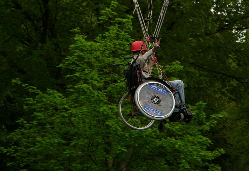 Ein Rollstuhlfahrer ist im Hochseilgarten unterwegs.