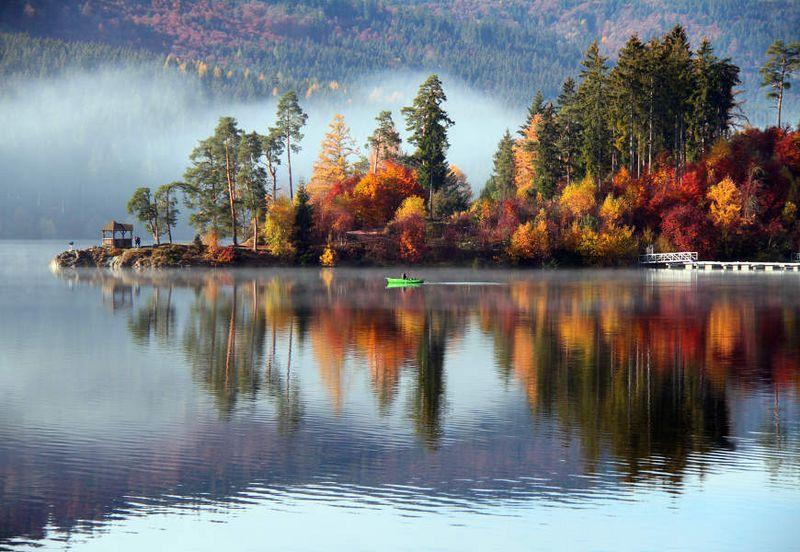 Herbsttag am Schluchsee im Naturpark Südschwarwald: Ein grünes Boot liegt auf dem Wasser und am Uferrand befinden sich zwei Menschen. Der Wald am Ufer ist bunt gefärbt und spiegelt sich im Wasser.