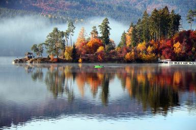 Der Schluchsee ist umgeben von herbstlich gefärbten Blättern. Auf dem See erkennt man ein kleines grünes Boot. Am Ufer auf der linken Seite stehen Menschen. Der herbstliche Wald spiegelt sich deutlich im See.